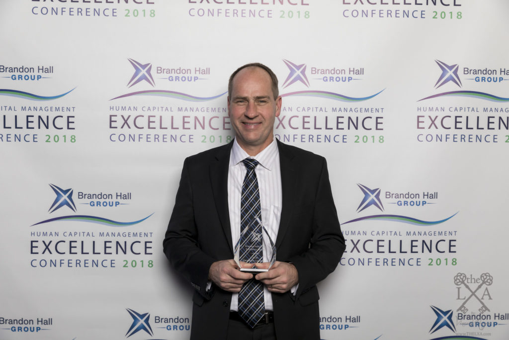 TiER1's CEO Greg Harmeyer accepts the Brandon Hall Group Excellence in Technology Award